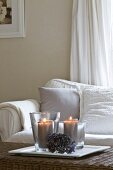 Lit candles on wicker table in front of comfortable sofa