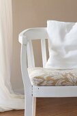 White-painted wooden armchair with floral seat cushion