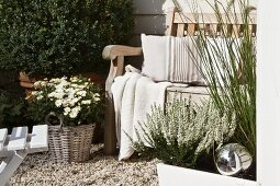 Seating area against house facade with potted plants and rustic wooden bench