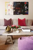 Modern painting in living room with natural textiles and simple wooden coffee table