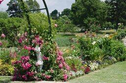Bunt blühende Blumenrabatte in weitläufiger Gartenanlage; im Vordergrund rankende Rosen und eine Steinfigur