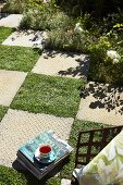 Chequered pattern of stone slabs and squares of lawn in sunny garden with flower bed to one side