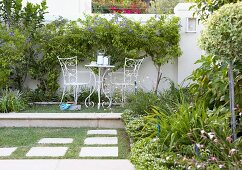 Delicate garden furniture on terrace platform; small, blue-flowering trees against white garden wall in background
