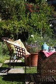 Sunny seating area in garden with metal furniture and chequered floor of stone slabs and lawn squares; teapot and teacups on table
