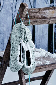 Crocheted slippers hanging on rustic chair in artificial winter atmosphere