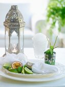 Oriental still-life arrangement of silver lantern, granita, peppermint and napkin in silver napkin ring