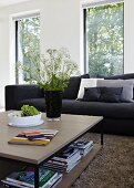 Square coffee table in front of black couch in living room with large windows; black vase of fresh wild flowers on table