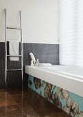 Bathroom with grey mosaic tiles on wall and bathtub decorated with floral mosaic