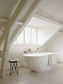 Minimalist bathroom with free-standing bathtub and long dormer window