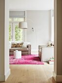 White arc lamp above grey living room sofa in pale interior with pink rug