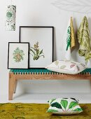 Botanical drawings leaning against wall on decorative, modern wooden bench and scatter cushions below patterned cloths hanging from hooks