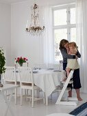 Mother and daughter in dining room with set dining table & chandelier