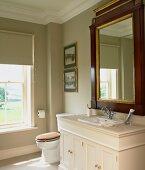 Classically elegant bathroom with antique, framed mirror on mushroom grey wall