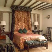 Canopied bed decorated with traditional fabrics in old half-timbered house