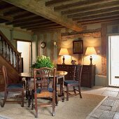 Antique furniture and foot of staircase in open foyer of rustic, half-timbered house