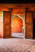 Mysterious light in Moroccan interior with open, ornate door and view through arched doorway into adjoining room