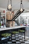 Bar stools with wrought iron and green seat cushions in front of breakfast bar under vintage, pendant gas lamps and staircase in background in open-plan interior