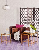 Brown leather armchair, retro nest of side tables and screen with pattern of circles