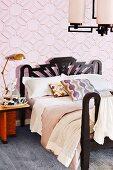 Doppelbett mit schwarzem Gestell an rosafarbener grafischer Mustertapete