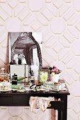 Vollgestelltes Schminktischchen mit nostalgischer schwarz-weiß Fotographie vor rosafarbener geometrischer Mustertapete