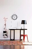 Red, retro metal stool at console table with table lamp; clock on wall in outline of tower