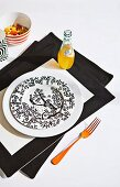 Black and white patterned plate and bottle of orangeade on black and white place mat with orange fork to one side