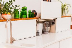 Storage space in cupboards with space-saving swing-up doors on Corian worksurface with integrated sink