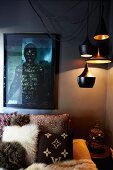 Dramatic lighting in corner of bedroom - various pendant lamps above ethnic scatter cushions on bed against dark-painted wall and photo of very dark-skinned person