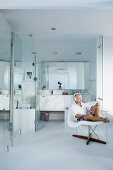 Man sitting on classic La Chaise chair in front of modern, glass bathroom area with marble washstand and mirrored cabinet