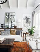 Pale, elegant living room with white, antique, upholstered armchairs and rustic coffee table in country-house ambiance