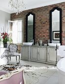 Two tall mirrors above vintage washstand cabinet against brick wall in shabby chic bathroom