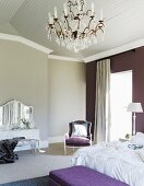 Traditional bedroom in elegant country-house style with crystal chandelier and one deep lilac wall