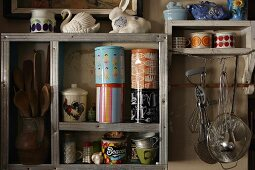 Collection of vintage cans and cooking utensils on simple, wooden kitchen shelves
