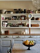 Ceramics, china crockery and framed photos on vintage-style dining room dresser; stemmed fruit bowl on simple wooden table in foreground
