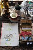 Drawing and weaving patterns surrounded by flea market collectors' items on rustic wooden table