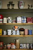 Collection of coffee cups, tea bowls and china jars on simple wooden shelves