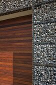 Gabion house facade and door of mahogany-coloured wooden slats