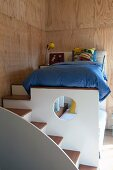Steps leading to child's loft bed in wood-clad room
