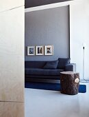 Elegant anthracite couch and rustic tree trunk side table on rich blue rug against grey wall