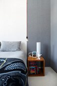 Cubic bedside cabinet made from exotic wood next to bed with pale grey bed linen against white wall; simple light bulb as pendant lamp