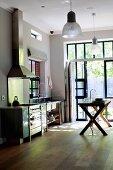 Minimalist kitchen with wooden table in front of open terrace door