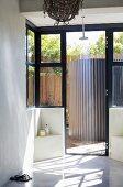 Minimalist shower with open door leading to terrace