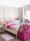 Bright girl's bedroom with white furniture and cheerful pink accents