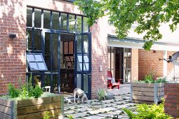 Contemporary brick house with large windows and shady terrace