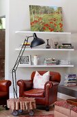 Reading corner with pale grey walls, brown leather armchair and original wooden table on castors; cheerful oil landscape painting on top shelf