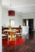 Weitläufiger Raum mit Essgruppe aus hellem Holz auf rotem, runden Teppich; im Hintergrund ein breiter Durchgang ins Wohnzimmer