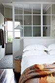 Gemütliches Doppelbett an Trennwand mit Innenfenster; im Hintergrund das Badezimmerfenster mit Holzfensterläden