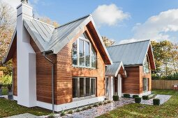 Modern, weatherboarded, twin-gabled, architect-designed house with zinc roof surrounded by lawns