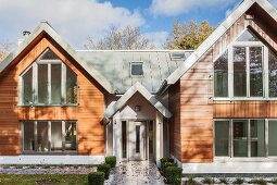 Front elevation of double-gabled, architect-designed house with wooden facade and zinc roof