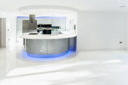 Modern rounded kitchen counter with white worksurface and blue plinth lighting in white interior